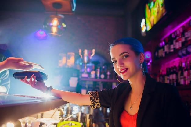 Przycięty obraz pracownica przyjmująca zapłatę od klienta za pośrednictwem nfc w barze