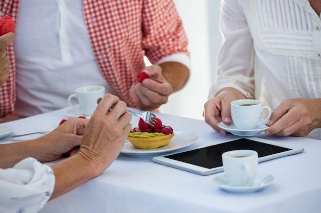 Przycięty obraz przyjaciół przy stole w restauracji