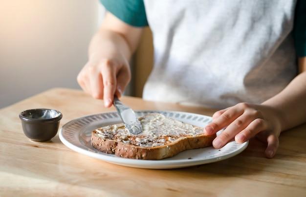 Przycięty obraz rąk dziecka rozprowadzającego masło na chlebie, dziecko nakładające masło na tosty na śniadanie dziecko przygotowuje jedzenie, heahty life stye concept
