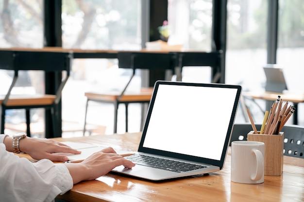 Przycięty obraz rąk kobiety pracy na komputerze przenośnym, siedząc przy stole.
