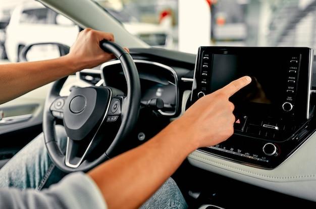 Przycięty obraz ręka człowieka za pomocą systemu nawigacji lub deski rozdzielczej podczas prowadzenia samochodu.