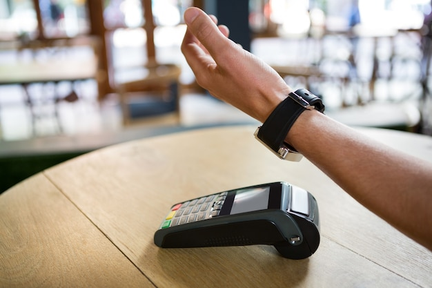 Przycięty obraz ręki człowieka za pomocą inteligentnego zegarka do wyrażania zapłaty w kawiarni