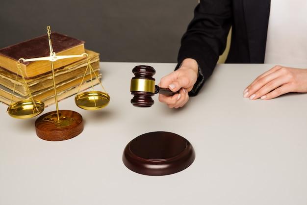 Przycięty obraz sędziego wydającego werdykt uderzając młotkiem w biurko.