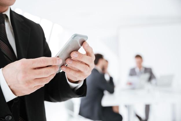 Przycięty obraz starszego mężczyzny trzymającego telefon w biurze z kolegami