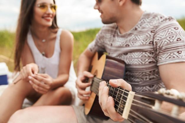 Przycięty Obraz Szczęśliwej Pięknej Pary Siedzącej Razem W Parku, Grającej Na Gitarze, Relaksującej Premium Zdjęcia