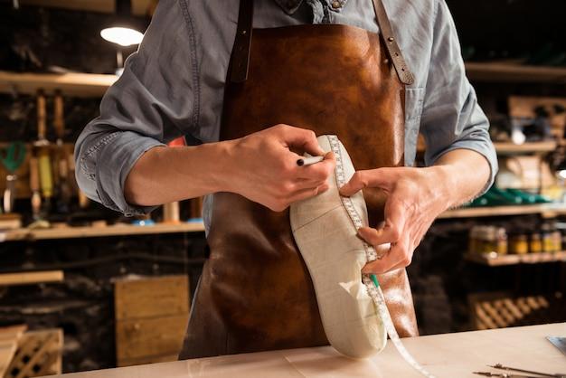 Przycięty obraz szewca mierzącego but