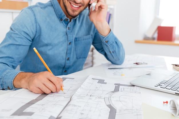 Przycięty obraz uśmiechniętego młodego biznesmena rozmawiającego przez telefon komórkowy i robiącego notatki siedząc w biurze