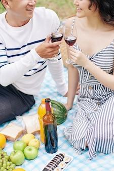 Przycięty obraz uśmiechniętej młodej pary azjatów wznoszącej tosty z kieliszkami czerwonego wina podczas romantycznego pikniku w walentynki