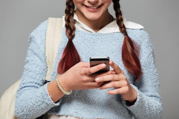 Przycięty obraz uśmiechniętej uczennicy z plecakiem