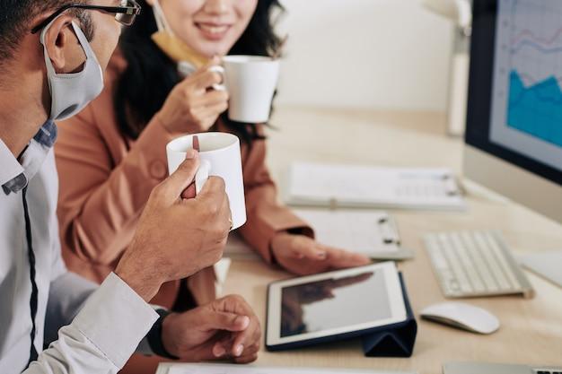 Przycięty obraz uśmiechniętych kolegów pijących kawę i omawiających raporty i wykresy na spotkaniu w biurze
