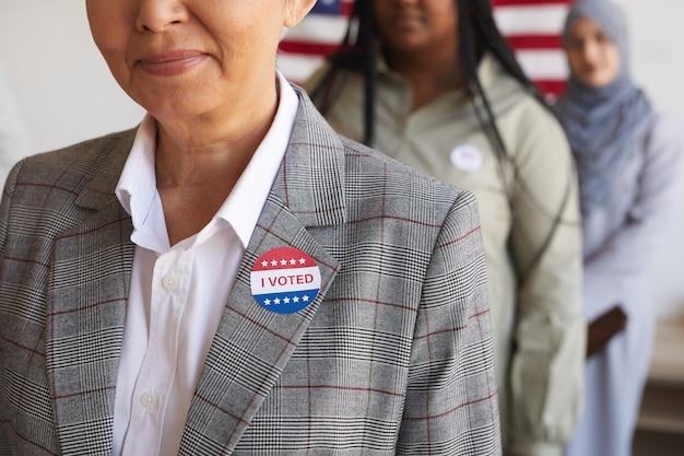Przycięty obraz wieloetnicznej grupy ludzi w lokalu wyborczym w dniu wyborów, skup się na uśmiechniętej starszej kobiecie z naklejką i głosuję na pierwszym planie, skopiuj miejsce