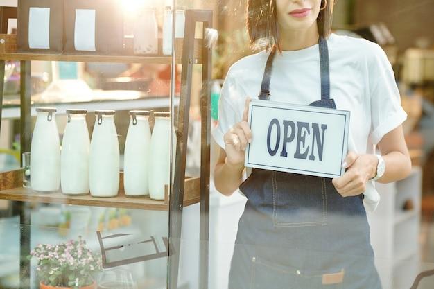 Przycięty obraz właścicielki sklepu trzymającej otwarty znak i witającej klientów w środku