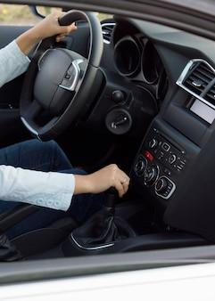 Przycięty obraz wnętrza samochodu przedstawiający dłonie kobiety zmieniające biegi podczas jazdy