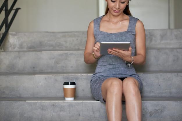 Przycięty obraz zajętej młodej azjatyckiej bizneswoman w szarej sukience siedzącej na schodach z kawą na wynos i używającej tabletu