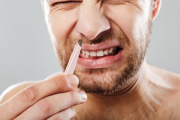 Przycięty obraz zmarszczonego brwi mężczyzny z bólu