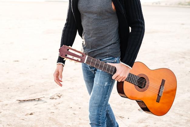 Przycięty obraz zwykłego mężczyzny trzymającego gitarę i idącego przez brzeg morza