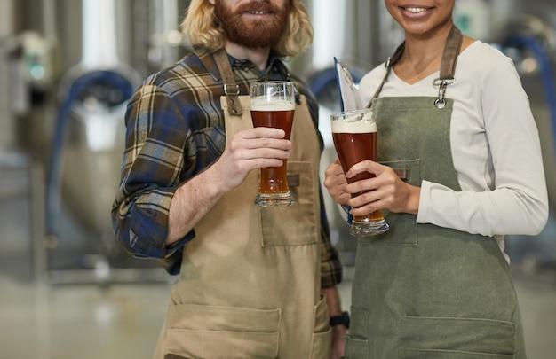 Przycięty portret dwóch uśmiechniętych młodych pracowników trzymających szklankę do piwa i patrzących na kamerę stojąc w warsztacie w fabryce browarnictwa, kopia przestrzeń