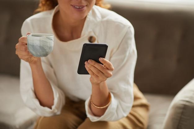Przycięty portret eleganckiej kobiety trzymającej smartfon i kubek kawy podczas przeglądania mediów społecznościowych, miejsce na kopię
