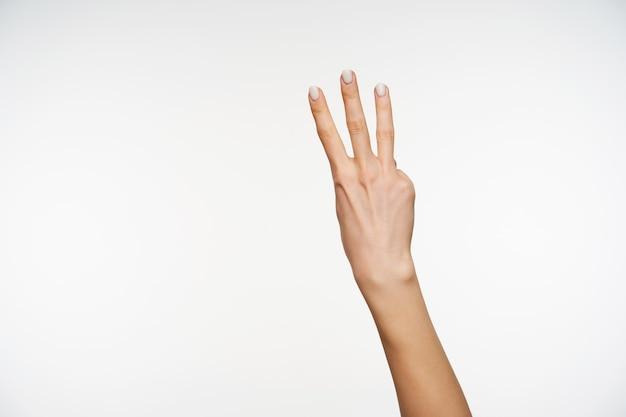 Przycięty portret kobiecej dłoni z białym manicure, trzymając trzy palce uniesione, pokazując liczenie gestów, jest na białym tle