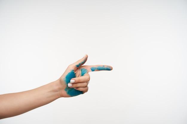 Przycięty portret kobiecej dłoni z niebieską farbą na nim podnoszona, wskazując palcem wskazującym do przodu, na białym tle