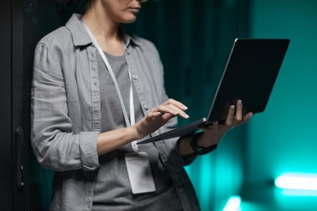 Przycięty portret kobiety inżynier danych trzymającej laptopa podczas pracy z superkomputerem w serwerowni, miejsce kopiowania