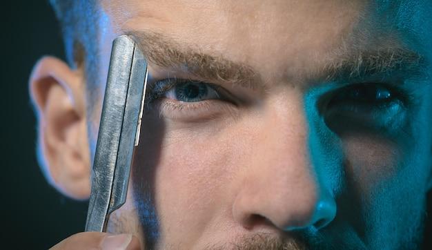 Przycięty portret młodego brutalnego brodatego mężczyzny z brzytwą w pobliżu oka stylowy fryzjer z