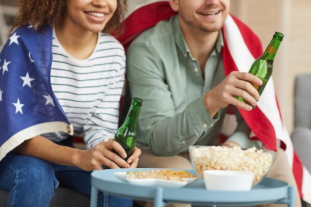 Przycięty portret młodej pary rasy mieszanej, oglądając telewizję w domu i pijąc piwo, mając na sobie amerykańską flagę