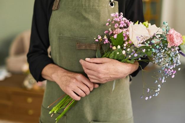 Przycięty portret nierozpoznawalnej kobiecej kwiaciarni trzymającej bukiet stojąc w kwiaciarni