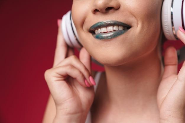 Przycięty portret radosnej punkowej dziewczyny z dziwaczną fryzurą i ciemną szminką uśmiechającą się podczas słuchania muzyki przez słuchawki izolowane nad czerwoną ścianą