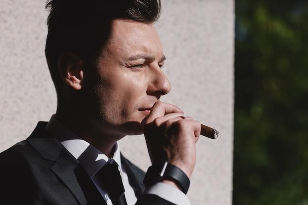 Przycięty portret twardego spojrzenia biznesmena podczas palenia kubańskiego cygara.