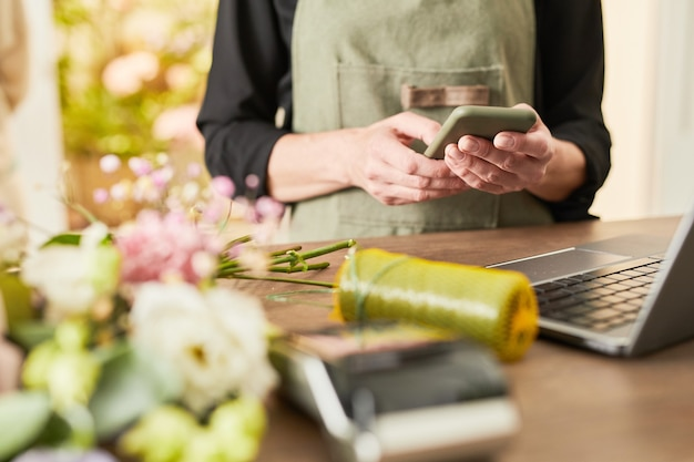 Przycięty portret właścicielki małej firmy korzystającej ze smartfona podczas zarządzania przestrzenią do kopiowania w kwiaciarni