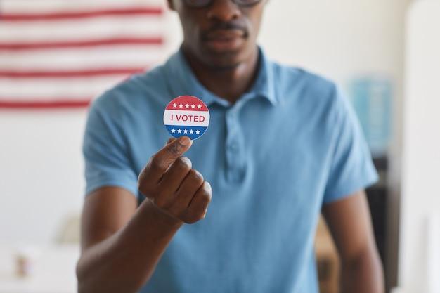 Przycięty portret współczesnego afrykańskiego mężczyzny trzymającego naklejkę i głosuję, miejsce na kopię