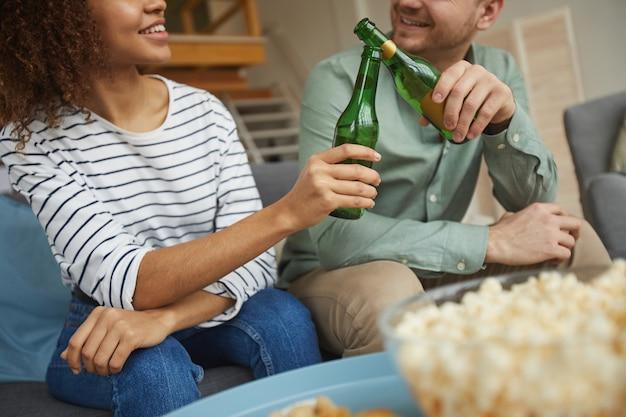 Przycięty portret współczesnej pary rasy mieszanej, oglądającej telewizję w domu i brzęczącej butelkami piwa, siedząc na kanapie w przytulnym mieszkaniu