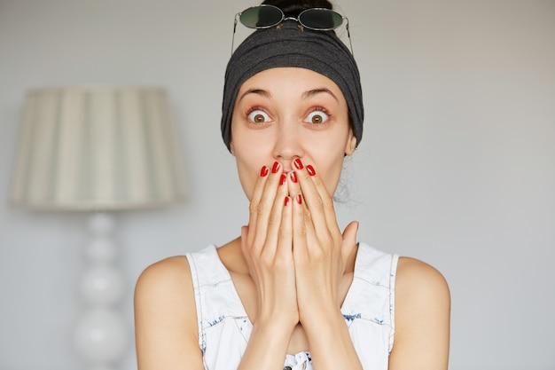 Przycięty portret zszokowanej dziewczyny zakrywającej usta