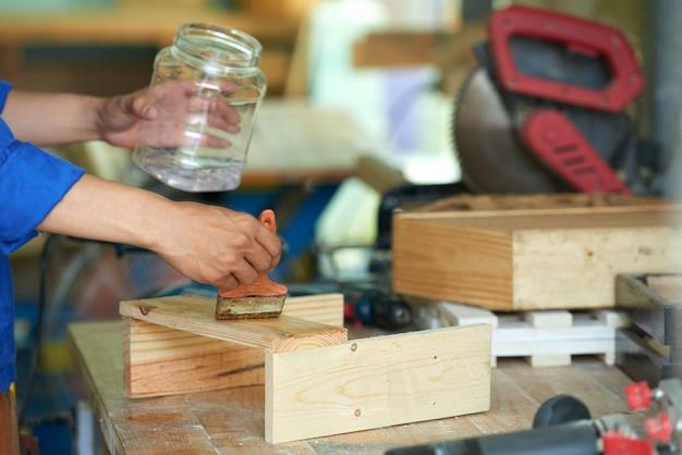 Przycięty stolarz polerujący drewno na stole warsztatowym