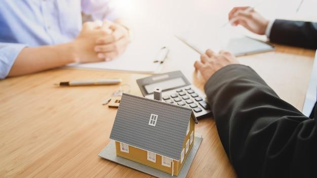 Przycięty strzał agent nieruchomości przedstawia klientowi na drewnianym biurku