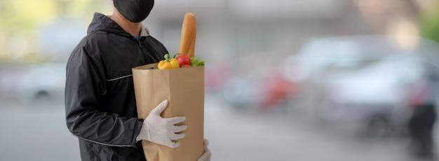 Przycięty strzał człowieka usługi dostawy żywności, trzymając torbę świeżej żywności