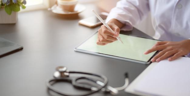 Przycięty strzał dla młodej kobiety lekarz pracuje nad dokumentacją medyczną i wyniki egzaminu z tabletem