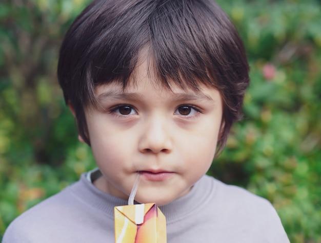 Przycięty strzał dziecko stojące w ogrodzie, picie soku, zdrowe dziecko chłopiec pije świeży sok.