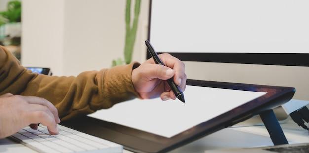 Przycięty strzał męskiego projektanta edytującego swój projekt na cyfrowym tablecie z pustym ekranem