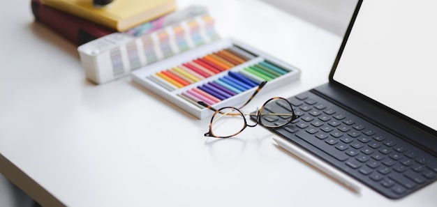 Przycięty strzał nowoczesny projektant pokoju biurowego z pustego ekranu cyfrowego tabletu i materiałów biurowych na białym stole