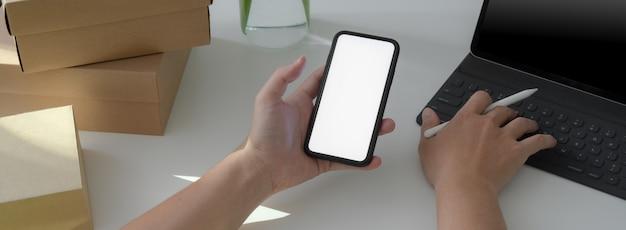 Przycięty strzał początkujących biznesmenów pracujących ze smartfonem, tabletem i pudełkami