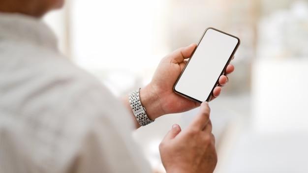 Przycięty strzał sms-y pusty ekran telefonu z niewyraźne pomieszczenie biurowe
