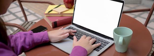 Przycięty strzał studentka uniwersytetu robi swoje zadanie z pustego ekranu laptopa i książek