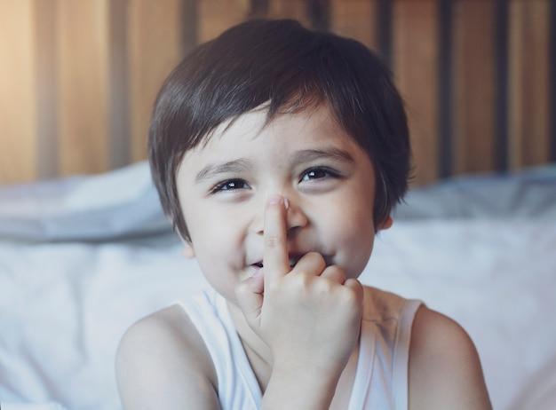 Przycięty strzał szczęśliwy mały chłopiec stosując krem balsam do ciała na nosie po prysznicu