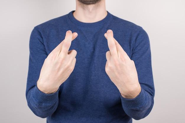 Przycięty szczegół portret niepewnego faceta, który robi skrzyżowany palec na białym tle szarej ścianie