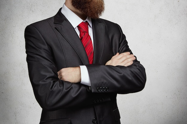 Przycięty widok atrakcyjnego, odnoszącego sukcesy przedsiębiorcy z gęstą brodą, stojącego z założonymi rękami w biurze i myślącego o czymś ważnym. obraz poważnego człowieka pewnie.