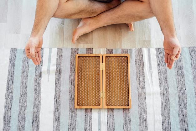Przycięty widok człowieka ćwiczeń jogi medytacji i siedzącego na podłodze w pobliżu deski sadhu