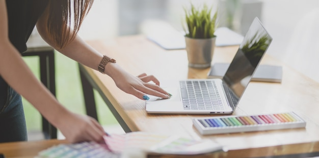 Przycięty widok kobiet projektanta pracującego nad projektem z laptopem