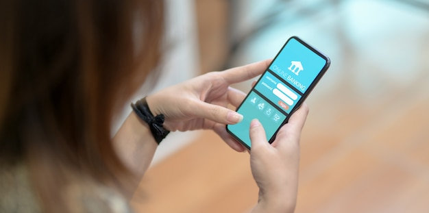 Przycięty widok kobiety robi bankowości internetowej na smartfonie